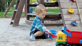 Slow motion video of cute smiling boy plating and digging sand in sandbox with red plastic shovel. Slow motion footage of cute smiling boy plating and digging stock footage