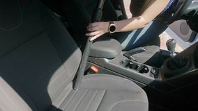 Slow motion video of female driver cleanming salon of her car with vacuum cleaner. Slow motion footage of female driver cleanming salon of her car with vacuum stock video
