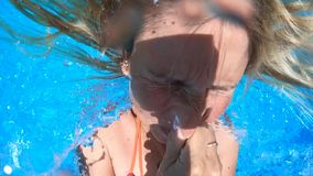 Woman jumping into a blue water pool stock footage