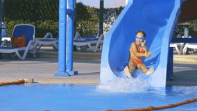 Girl on waterslide in aqua park pipe. Slow motion video of a happy little caucasian girl on waterslide in aqua park pipe stock video footage