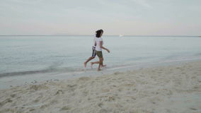 Slow motion video of happy man and woman running on the exotic beach stock footage