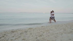Slow motion video of happy man and woman running on the exotic beach stock video footage