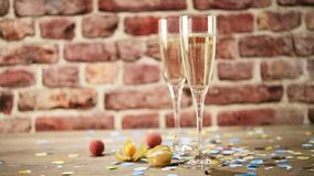 Slow motion video of a lot of confetti following down on two flutes of champagne on the wooden table with the brick background, se. Slow motion video of a lot of stock video