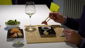 Slow motion video of man with a beard eating sushi and drinking white wine during the dinner stock video footage