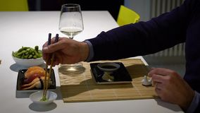 Slow motion video of man with a beard eating sushi and drinking white wine during the dinner stock footage