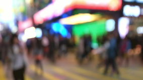 Slow motion video of people moving at crossroad in crowded evening city street. Hong Kong stock video