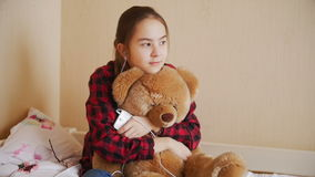 Slow motion video of teenage girl sitting with teddy bear on bed and listening to music stock footage