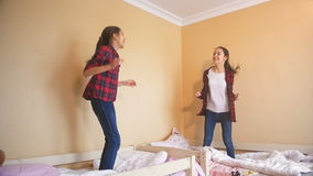 Slow motion video of two cheerful sisters jumping on bed at bedroom. Slow motion of two cheerful sisters jumping on bed at bedroom stock video footage