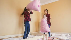 Slow motion video of two teenage girls fighting with pillows stock video