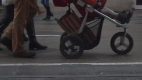 Slow motion video of unrecognizable people with baby carriage in the street stock footage