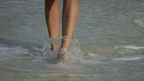 Slow motion video of a woman walking on beach barefoot at sunrise. Towards the camera. long shot stock footage