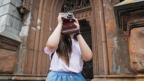 Slow motion video of young smiling woman making photographs of old town on manual film camera