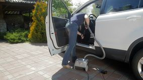 Slow motion video of young woman cleaning her car with vacuum cleaner at house backyard. Slow motion footage of young woman cleaning her car with vacuum cleaner stock video