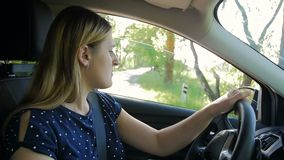 Slow motion footage of young woman reversing and turning on road. Driver looking at side view mirrors. Slow motion video of young woman reversing and turning on stock video