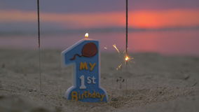 Slow motion view of candle and two sparklers standing in the sand on beach against blurred sunset. Slow motion view of first years birthday candle and two stock footage