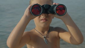 Slow motion view of small boy watching with binoculars against blurred sea. Slow motion view of small boy watching with binoculars with red glasses on landscape stock video footage