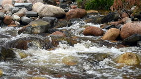 Slow motion water flowing over rocks. In mountain stream stock video footage
