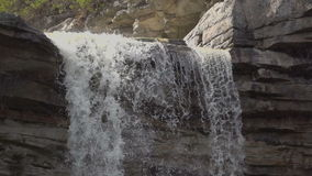 Slow motion water pouring over a waterfall. Slow motion water pouring over the Awosting waterfall stock video