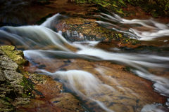 Slow motion waterfall. Water cascading over stones or rocks with slow motion blur effect stock image