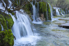 Waterfalls Over Moss in Slow Motion in Juizhaigou. Blurred slow motion of multiple waterfalls rushing over moss covered rocks into a stream in Jiuzhaigou Reserve royalty free stock image