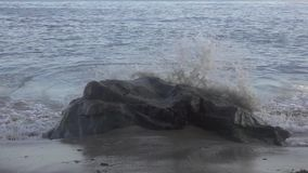 Slow Motion Wave. A Slow Motion Wave Crashing Over A Rock On A Beach stock footage