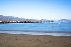 Slow motion waves in Santa Barbara bay. Image of a long exposure in Santa Barbara Harbor California with famous Stearns Wharf lining the blue water Royalty Free Stock Photo