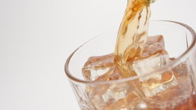 SLOW MOTION: Whiskey pour in a glass with an ice cubes on white background - close up stock video footage
