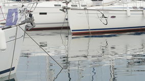 Slow Motion. White yachts in harbor, reflections in calm water, blue morning sky stock video