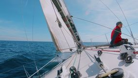 Skipper or sailor captain sits on sailboat deck. Slow motion wide beautiful shot of man or professional sailor or amateur sea lover sit on deck of sailboat under stock video