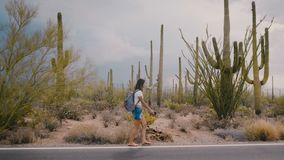 Slow motion wide shot, happy young adult tourist woman walking along amazing wild cactus desert road in national park.