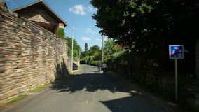 Slow motion - Woman cycling on road through village in France stock video