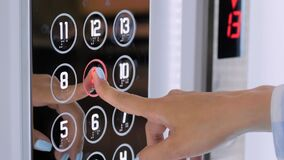 Slow motion: woman finger pressing elevator button of ninth floor