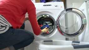 Slow Motion Of Woman Loading Clothes Into Washing Machine stock video