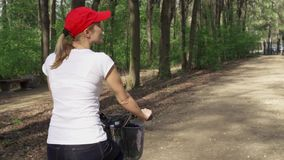 Slow Motion. Woman riding bike. Female teenager biking cycling in sunny park. Active sports concept stock video footage