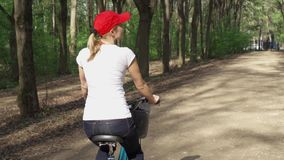 Slow Motion. Woman riding bike. Female teenager biking cycling in sunny park. Active sports concept. Slow Motion. Sportive woman in red cap and white t-shirt stock footage