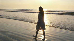Slow motion of woman walking barefoot on wet sea shore during sunset
