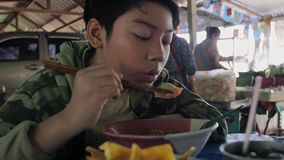 Slow motion of Young asian boy eating noodle by chopstick at restaurant. stock video