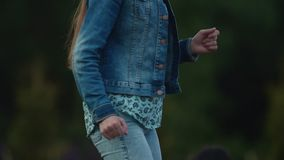 Slow motion young beautiful girl dancing in front of trees at music festival. Slow motion young beautiful caucasian girl in denim jacket dancing in front of stock video footage