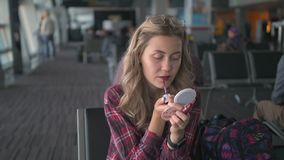 Slow Motion A young beautiful girl in a red checkered shirt, paints her lips with red lipstick with a brush and looks at. Herself in a small mirror sitting in stock video footage