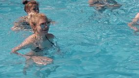Girls are engaged in water aerobics. Jumping. stock video footage