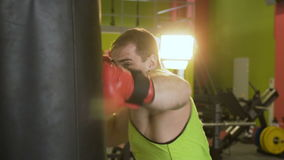 Slow motion of young boxer man practicing on a punching bag stock video