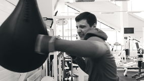 Slow motion of young boxer man practicing on a punching bag in sport fitness club stock video