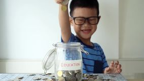 Children education concept with money jar. Slow motion young boy drops coin money into glass jar with education label, financial concept stock video footage