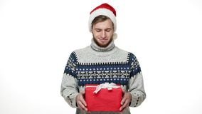 Slow-motion young caucasian man giving surprise christmas gift to camera. Slow-motion young caucasian man giving surprise christmas gift to camera stock footage