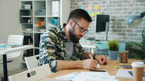 Slow motion of young designer working in office writing sitting at desk alone stock footage