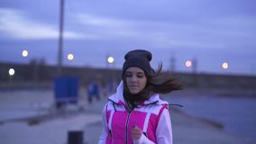 SLOW MOTION: A young girl in a sports hat and jacket makes a morning jog on the embankment in the morning before the dawn of the s