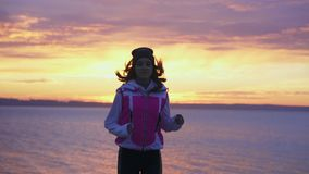 SLOW MOTION: A young girl in a sports hat and jacket makes a morning jog on the embankment in the morning