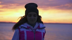 Slow motion: a young girl in a sports hat and jacket makes a morning jog on the embankment in the morning stock footage