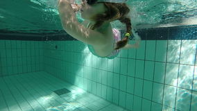 Slow motion of young girl swimming underwater and doing a twist stock footage
