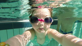 Slow motion of young girl swimming underwater with goggles stock video
